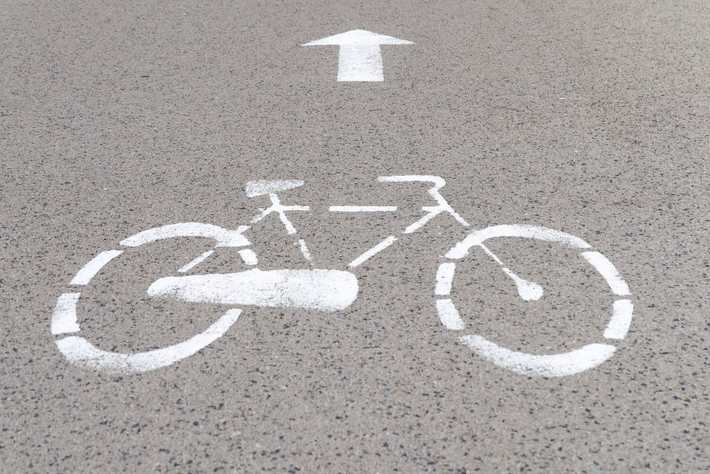 Road mark on asphalt indicating reserved bike path, grey background, bicycle silhouette and straight arrow